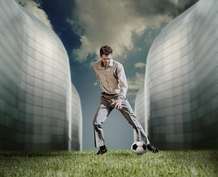 jugando futbol: Hombre en traje casual de juego en el fútbol cerca del moderno edificio Foto de archivo