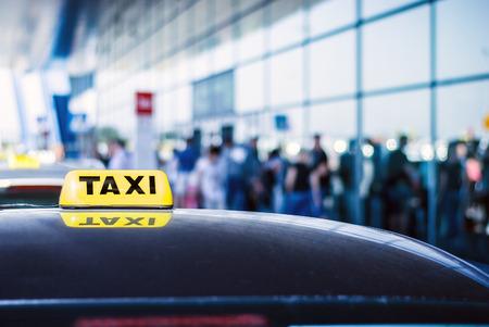 gente aeropuerto: Coche del taxi en espera de la llegada de pasajeros en frente de la puerta del aeropuerto Foto de archivo