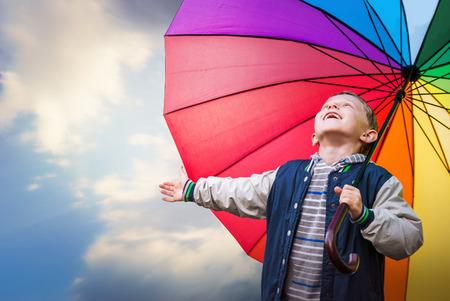 rain umbrella: Happy boy portrait with bright rainbow umbrella Stock Photo