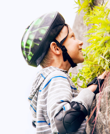 Boy practicing climbing outdoor on the stone wall photo