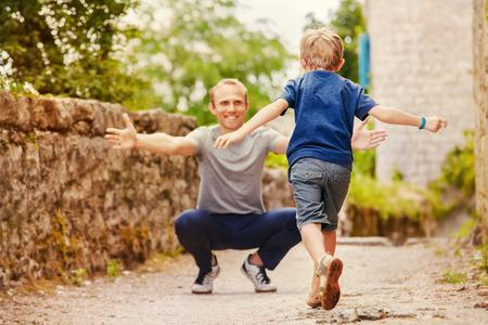 Zoon loopt naar papa s armen Stockfoto
