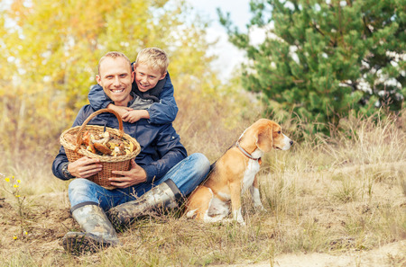 Father and little son happy with full basket of mushrooms