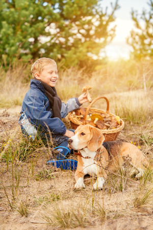 Little mushrooms pickers. Boy and beagle dog rest on the forest glade photo