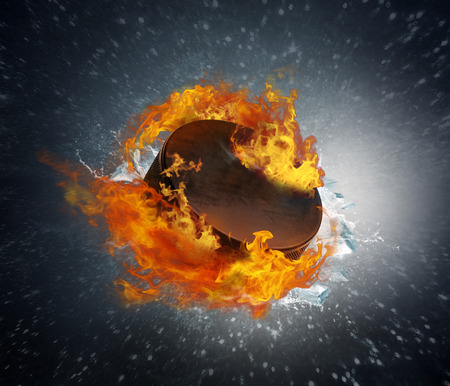 Burning puck with shards of ice on abstract background photo