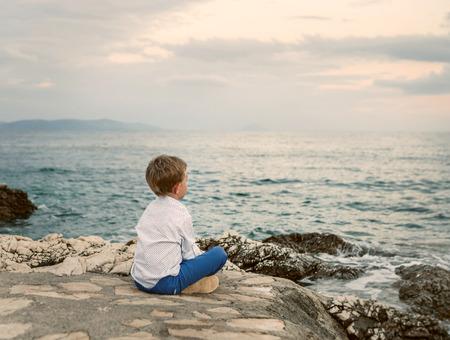 Little boy looks on the sunset sea landscape Standard-Bild