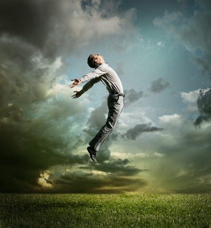 Young man jumping up to Sky photo