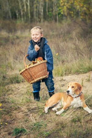 Happy Little boy with basket full of mushrooms with the dog on forest glade photo