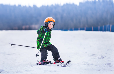narciarz: Little boy slides on skis down along the snow slope