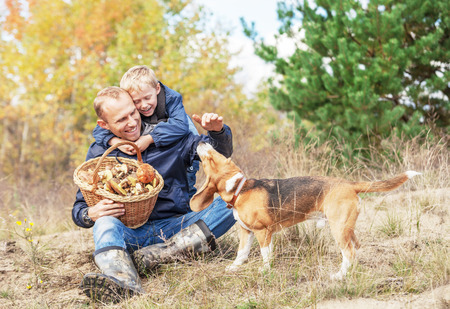 Father with son playing with dog on autumn forest glade