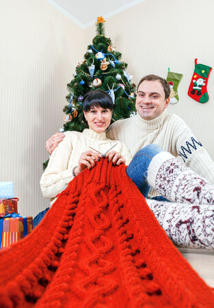 Happy couple under christmas tree with knitting work  photo