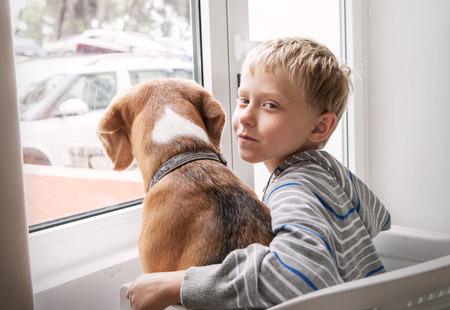 Niño pequeño con su perro esperando juntos cerca de la ventana