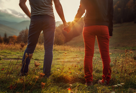Two teens hand in hand romantic walk by the autumnal mountains photo