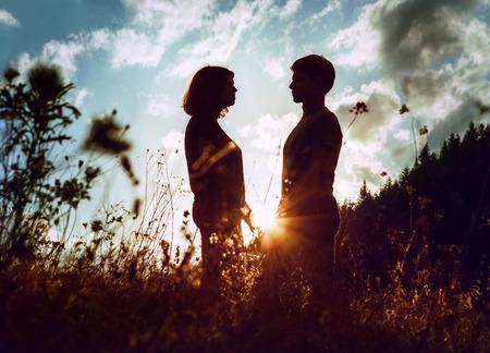 mujer enamorada: Silouettes la salida de dos personas jóvenes inlove Foto de archivo
