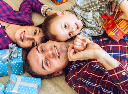 Happy smiling young family with gifts lying on the floor photo