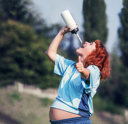 Active pregnant woman drinking water photo