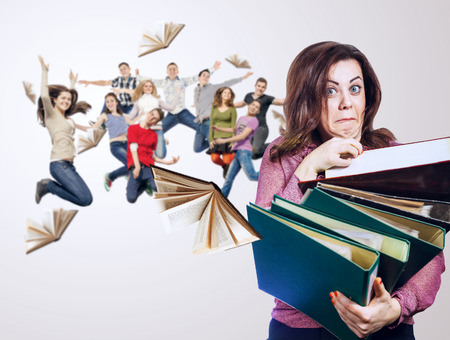 overloaded: Mad faced teacher with folders in hands and her jump pupils Stock Photo
