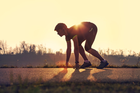 start position: Athletic man starting evening jogging in sun rays