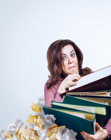 Mad faced teacher with folders in hands photo