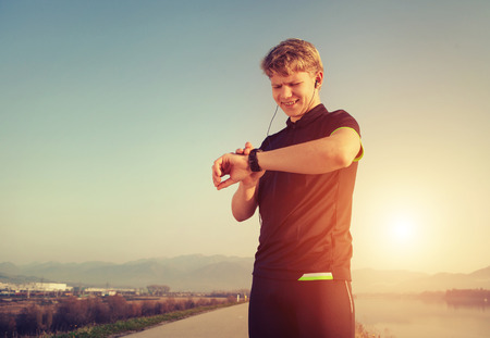 heart monitor: Runner starts his modern stopwatch before jogging Stock Photo