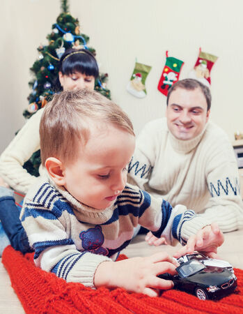 Boy playing with toy cars with his parents under the christmas tree photo