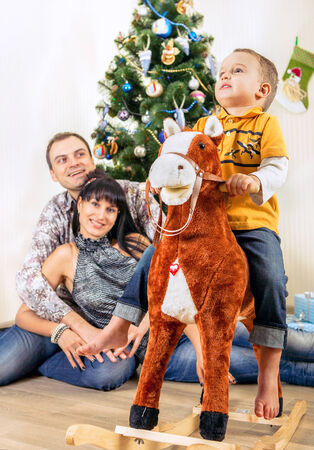 Little boy on toy horse with his parents under the Chrismas tree photo