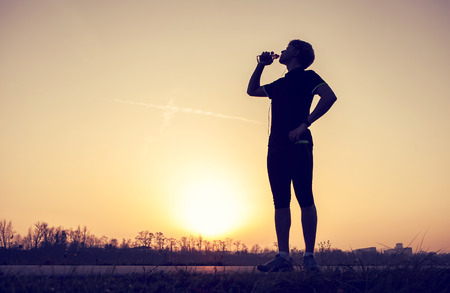 man drinking water: Runner drinks water after training Stock Photo