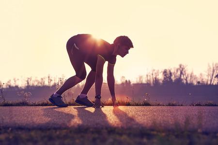 hombre deportista: Hombre atl�tico partir trotar por la noche en los rayos del sol Foto de archivo