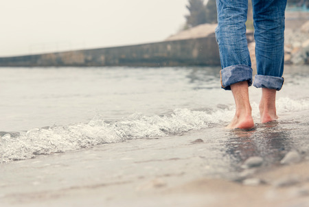 Close up image barefoot man legs in the sea surf