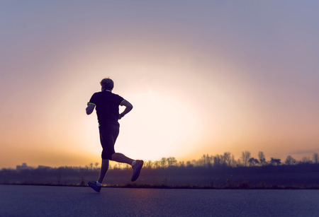 jogging in nature: Running man silhouette in sunset time