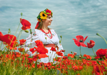 Young ukrainian woman on the field of poppies photo