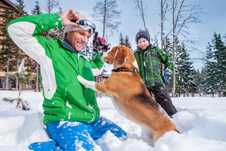 Father with son playing with their dog in deep snow photo