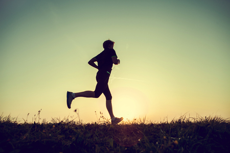 sun track: Running man silhouette in sunset time