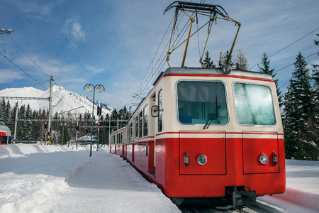 railway history: Red train on the mountain stantion in winter Stock Photo