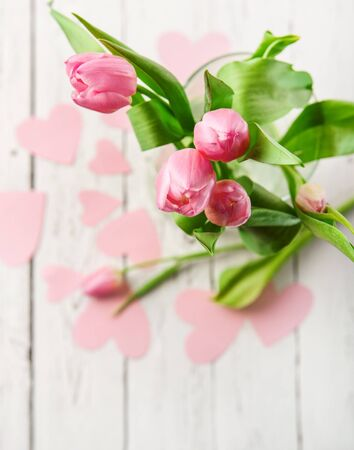 Pink tulips bouquet in vase on white wooden table photo