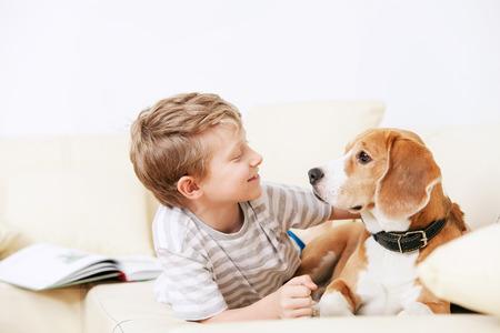 Deux amis - garçon et le chien couchés ensemble sur le canapé