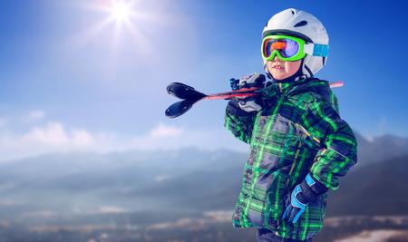 Boy en el equipo de esquí completo en la vista a la montaña