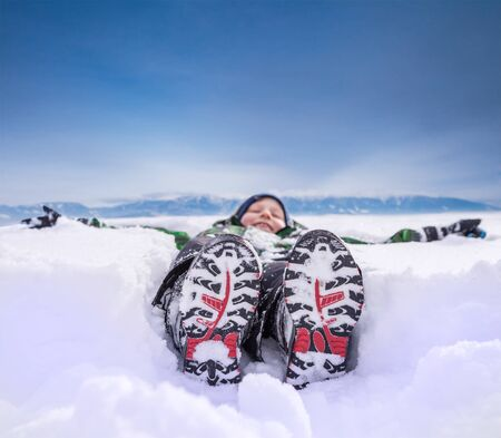Boy lying in deep snow on the mountain hill photo