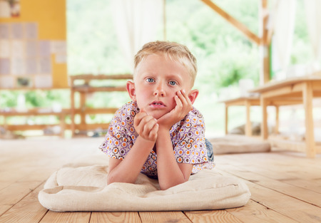 Bored boy lying on the wooden terrace on summer day photo