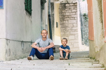 little town: Father and little son siting on the Old Croatian town street