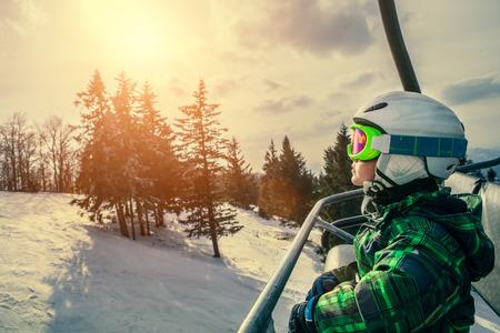 ski goggles: Little skier on the ski lift Stock Photo