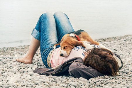 Beagle puppy sleeping on his owner breast at the sea side