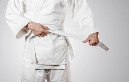 Judoka tying the white belt (obi)