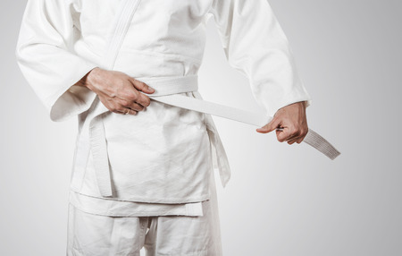 arts: Judoka tying the white belt (obi)