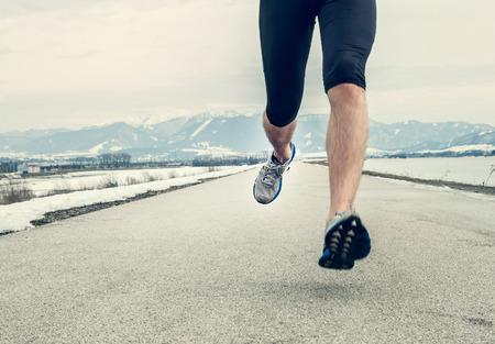 close up image: Close up image runner legs on asphalt