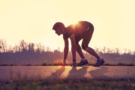 Homme athlétique commençant le jogging du soir dans les rayons du soleil