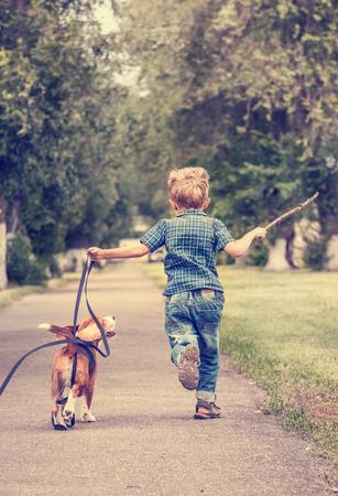niños caminando: Niño jugando con su cachorro beagle