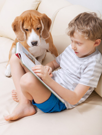 house pet: Boy reading for his dog at home