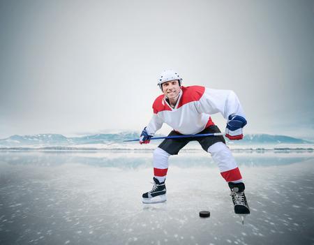 ice hockey player: Smiling hockey player on frozen lake ice