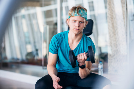 volition: Teenager in the Gym working with dumbbells