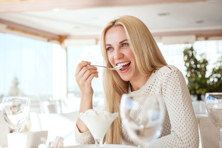 white cream: Beautiful young woman eating ice-cream in cafe Stock Photo